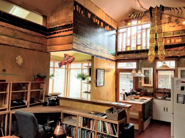 Room with vaulted ceiling, kitchen on the right side of the photo, desk in foreground and sunroom in background. The walls are abstractly painted. There is bookshelf full of books to the right of the desk.