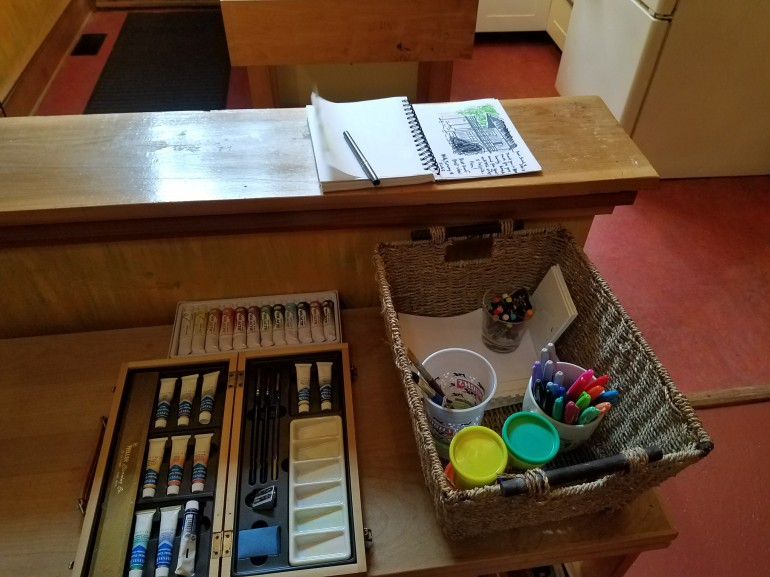 A set of paints, plus colored markers, play-doh, paper and the visitor's guest book.