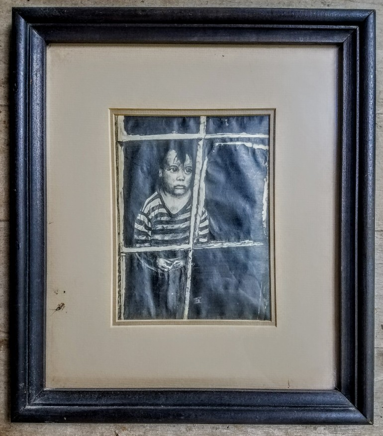 A framed drawing of a boy looking through a window.
